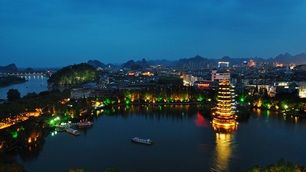 illuminated establishments along the river at dusk in Guilin