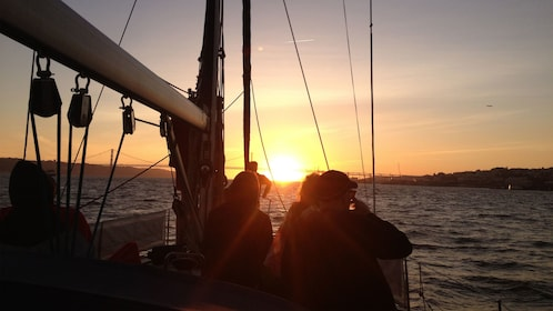 sailboat passengers looking at the sunset in Lisbon