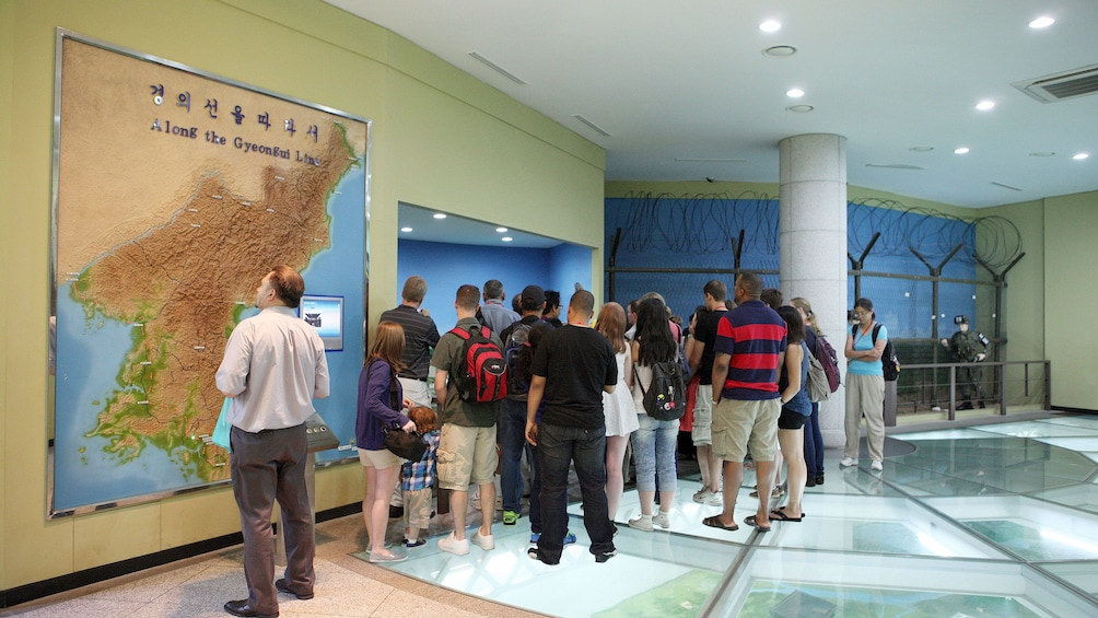 Show item 2 of 5. tour group observing map in seoul