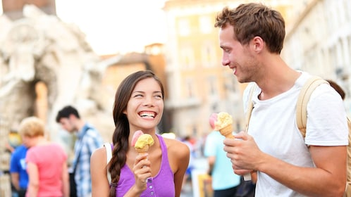 Happy couple enjoying delicious gelato on a hot, sunny day in Rome.
