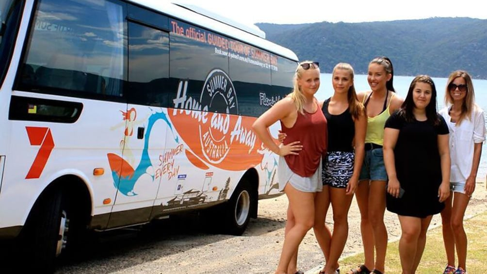 Show item 1 of 9. Home and Away tour group pose next to tour Bus.