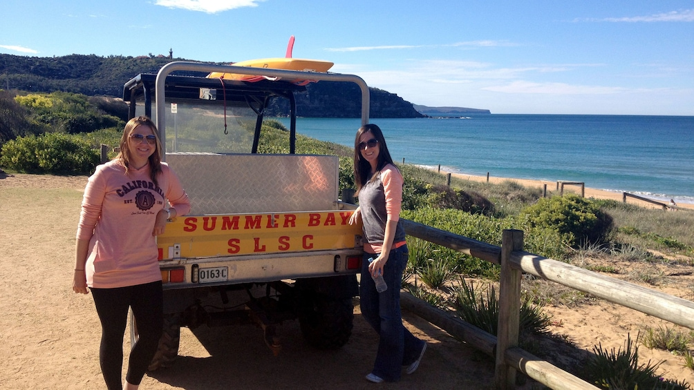 Show item 4 of 8. Two ladies take a picture in front of a car with a Summer Bay SLSC sign on the Summer Bay Home and Away location