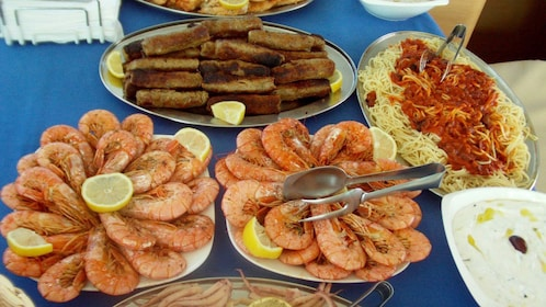 Plates of shrimp and pasta aboard a private sailing tour in Santorini