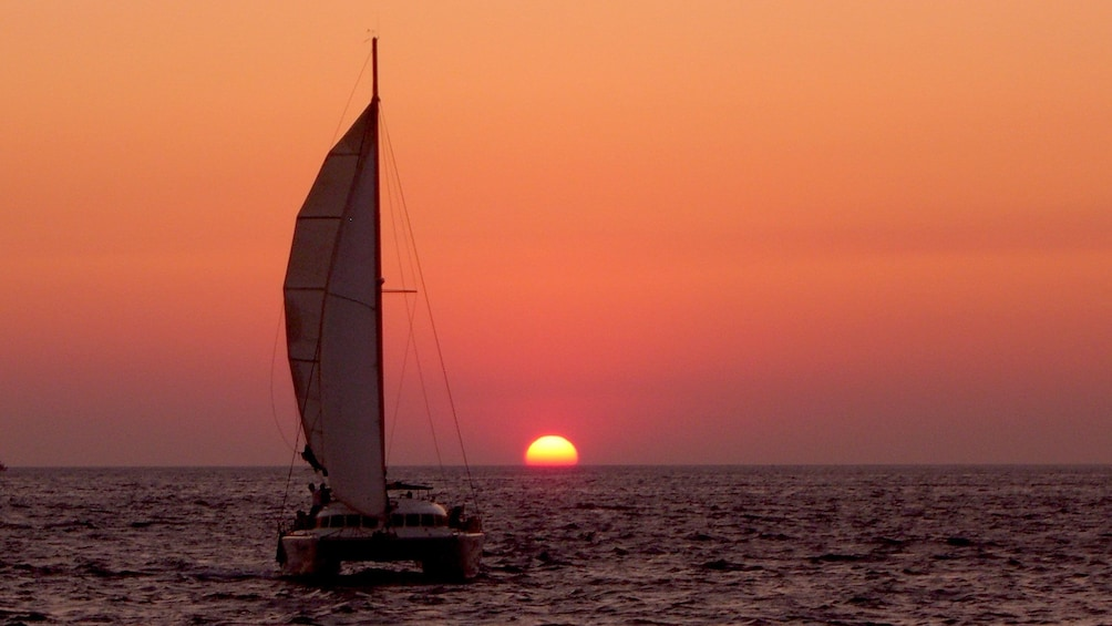 Show item 3 of 9. Sunset view of a catamaran on the waters in Santorini