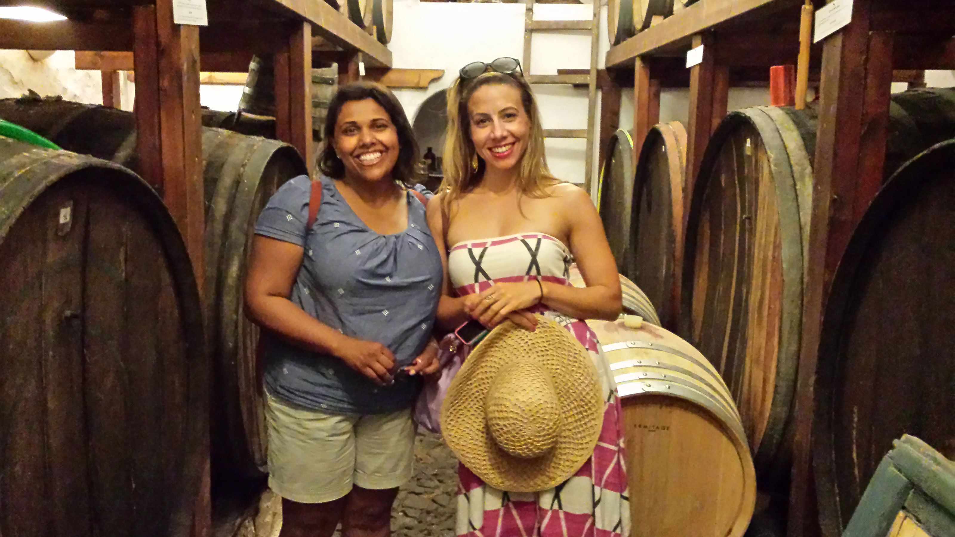 Two women standing at a wine cellar in Santorini