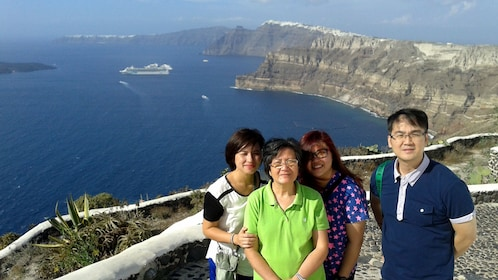 Family takes a picture at a viewpoint overlooking Santorini