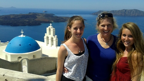 Family smiles for a picture overlooking beautiful Santorini