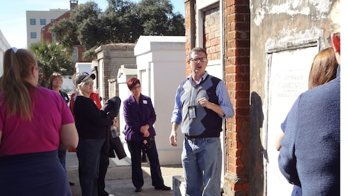 tour guide leading group of people on cemetery tour in New Orleans