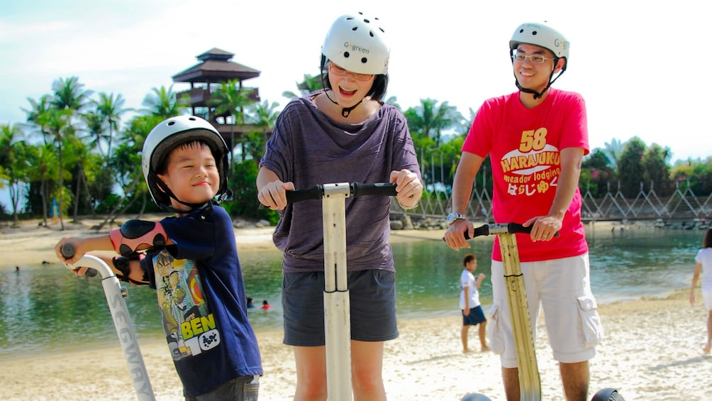 Show item 2 of 5. Family with young boy on segways at beach in singapore