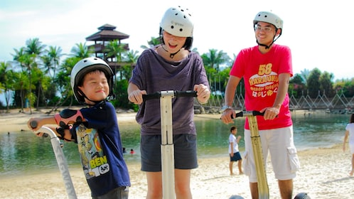 Family with young boy on segways at beach in singapore