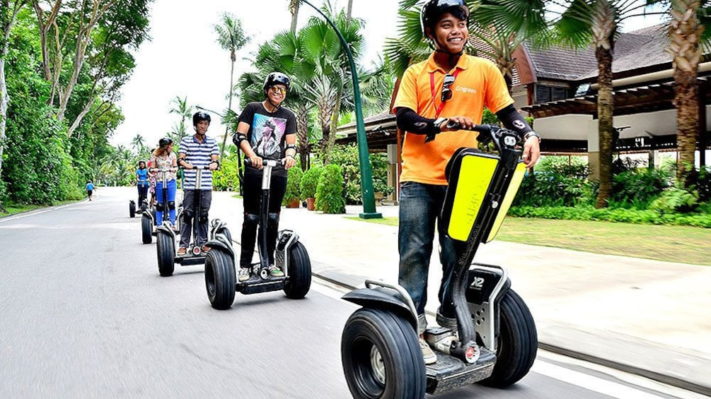 Show item 4 of 5. group on segways on streets of singapore