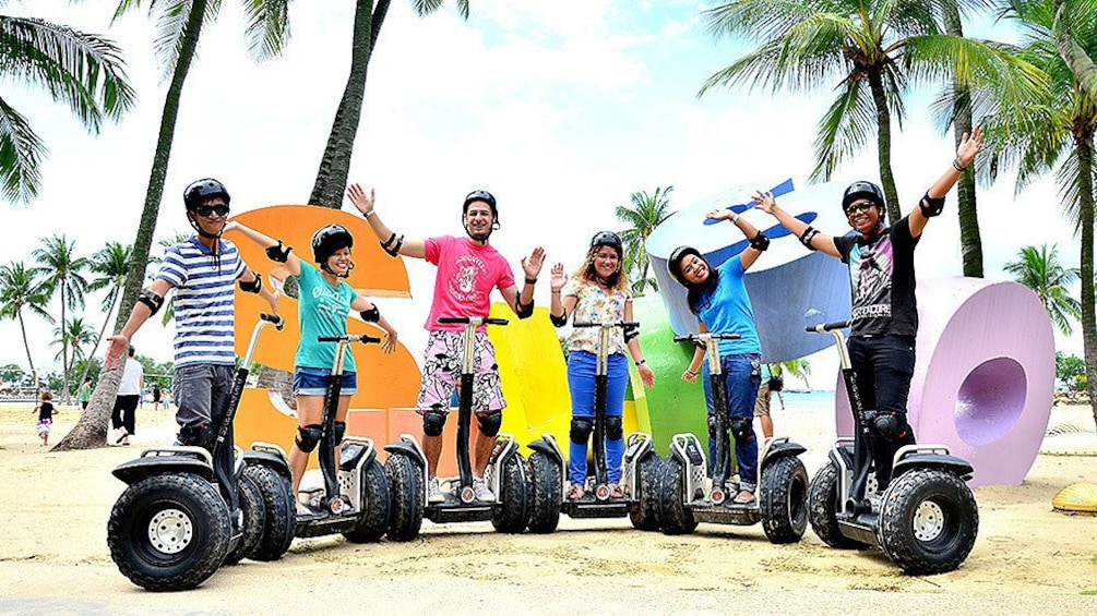 group on segways parked in front of sculpture in singapore