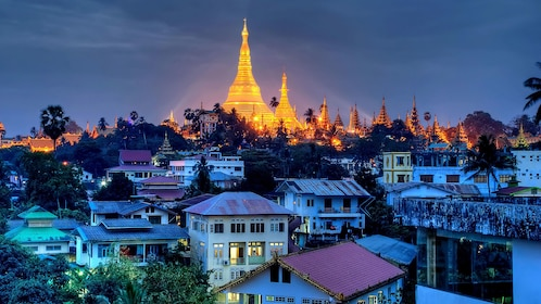Golden stupa of Shwe Dagon Pagoda shining at night with the city in the foreground in Yangon