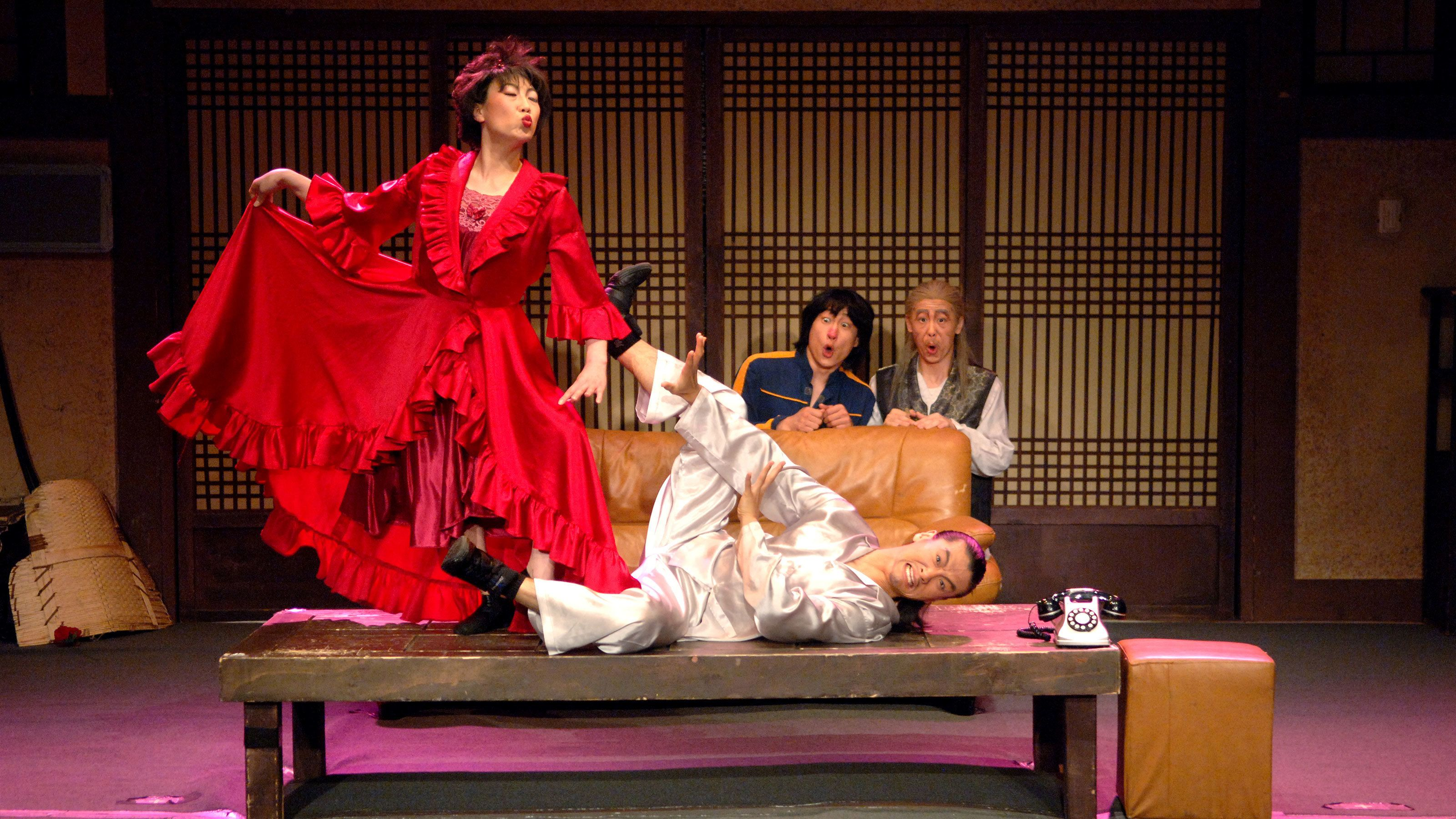 woman in red dress on stage with other performers in Seoul