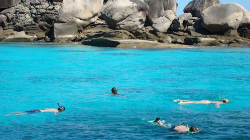 Tourists snorkeling in the waters of Similan Islands in Thailand