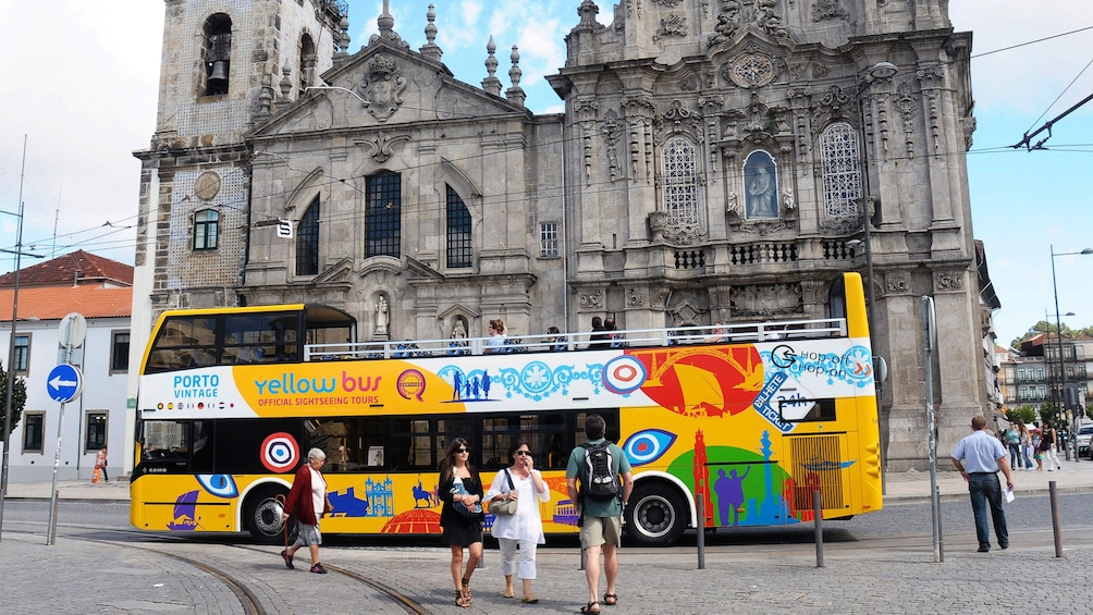 Show item 3 of 6. Hop-Of Hop-Off bus parked by a gothic cathedral in Porto
