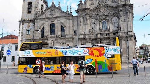 Hop-Of Hop-Off bus parked by a gothic cathedral in Porto