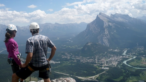 Two climbers enjoying majestic views from the summit of Mount Norquay