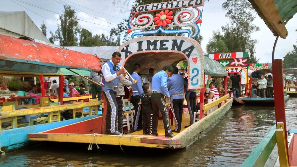 Show item 1 of 10. Musicians performing on colorful boats on the Xochimilco Canals