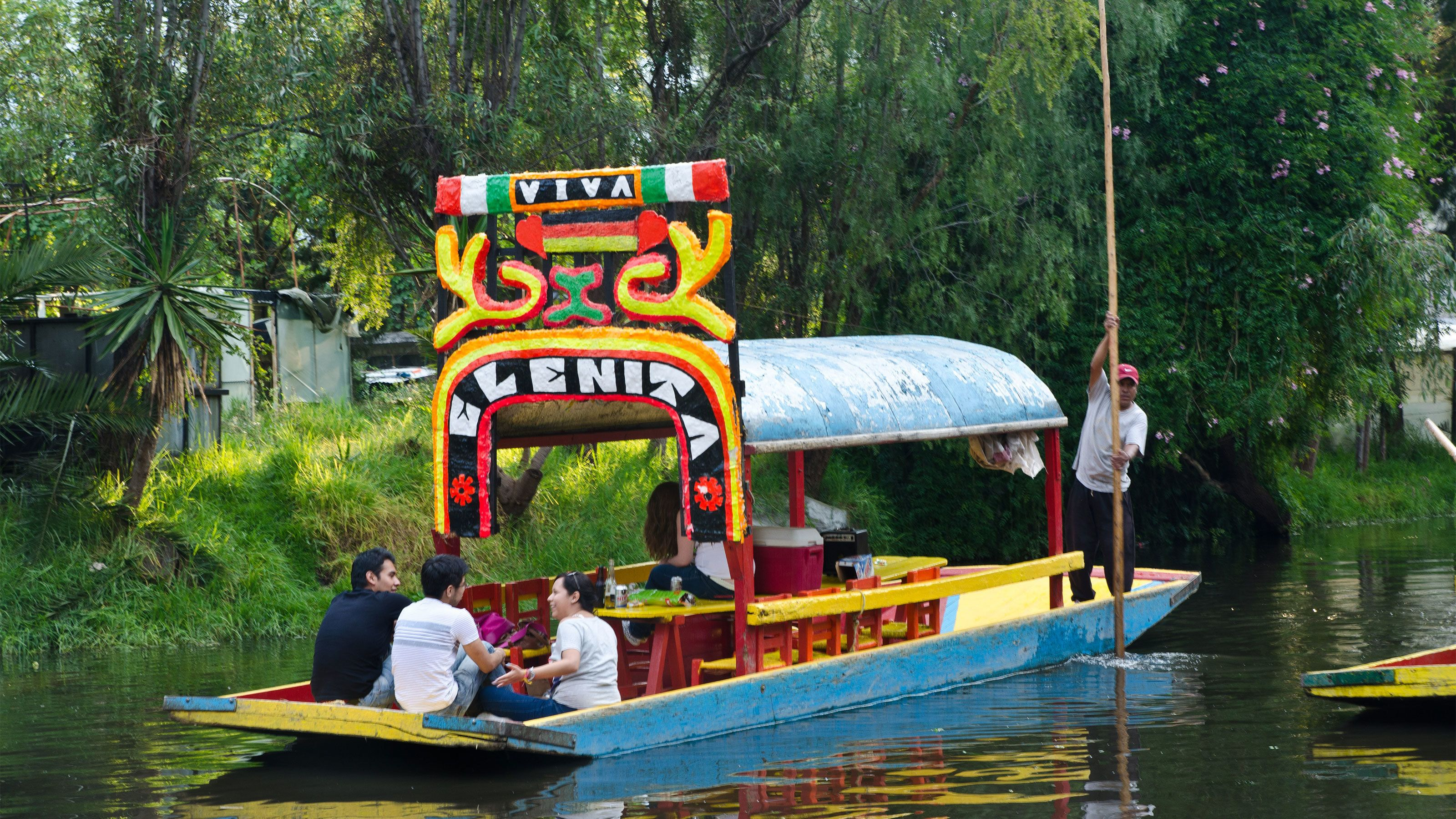 Small group of people on a colorful boat sailing down the Xochimilco Canals