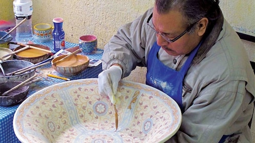 Man hand painting an elaborate design on a bowl in Puebla