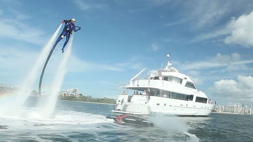 A man enjoying the thrill of flying with a Jetpack backpack in Sydney with a boat off to the right in Sydney