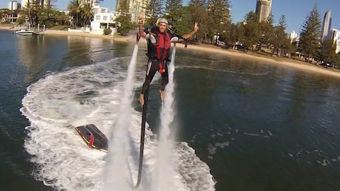A man enjoying the thrill of flying with a Jetpack backpack in Sydney while holding up two peace signs