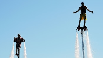Show item 3 of 6. Close up view of two individuals enjoy flying in the water with jetpacks and flyboards on in Australia
