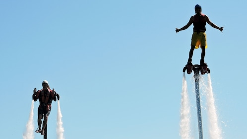 Close up view of two individuals enjoy flying in the water with jetpacks and flyboards on in Australia