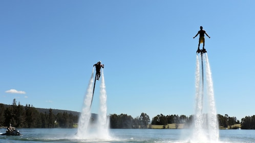 Two individuals enjoy flying in the waters with jetpacks and flyboards on in Australia