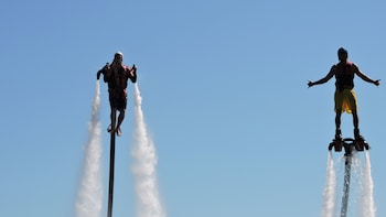 Show item 6 of 6. Close up view of two individuals enjoy flying in the water with jetpacks and flyboards on in Australia