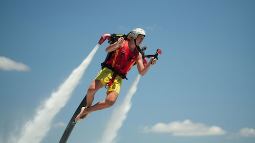 Young man flying in the air from his jetpack experience in Australia