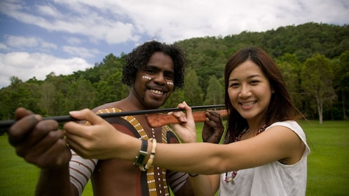 Guest smiles as she stands next to a tour guide at the Tjapukai Aboriginal Cultural Park in Cairns