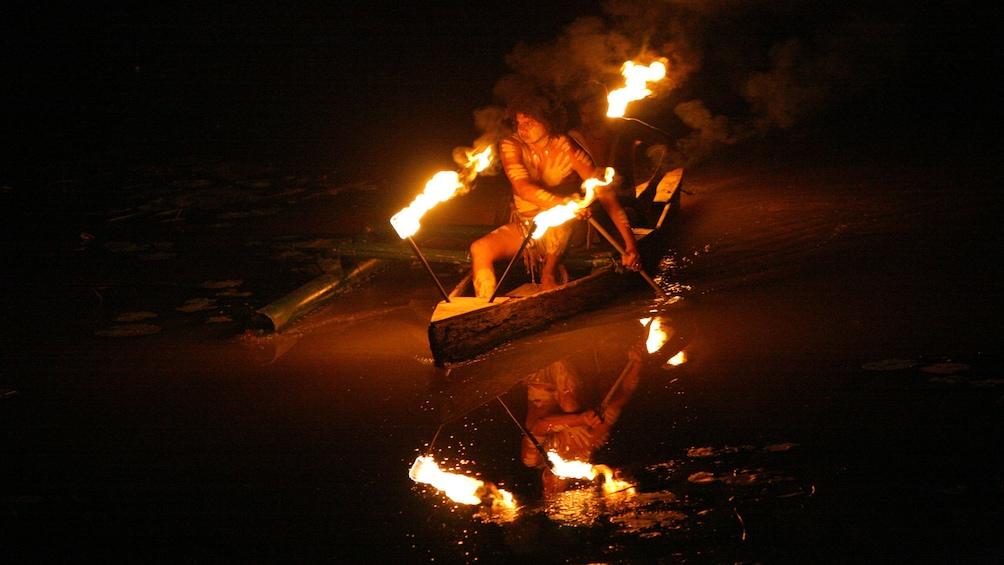 Show item 4 of 5. Man rowing in a canoe at the Tjapukai Aboriginal Cultural Park