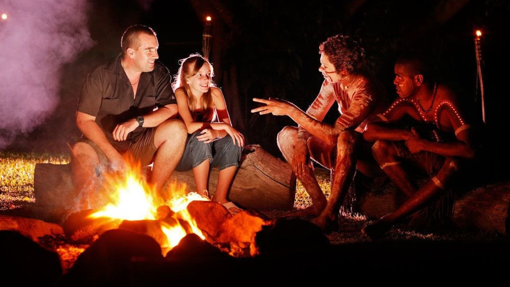 Show item 5 of 5. Guests sitting near the fire pit while performers at the Tjapukai Aboriginal Cultural Park chat with them