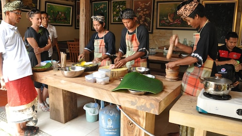 People observing  men cook a traditional meal in Bali