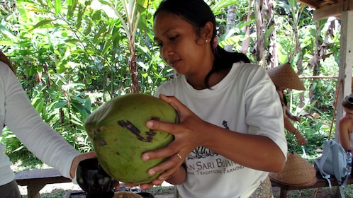 Woman opening a coconut in Bali