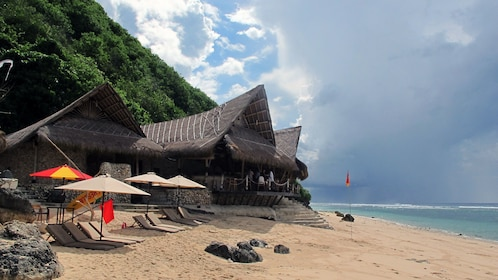 Bar and chaise lounges on a sandy beach at Bukit Peninsula in Bali