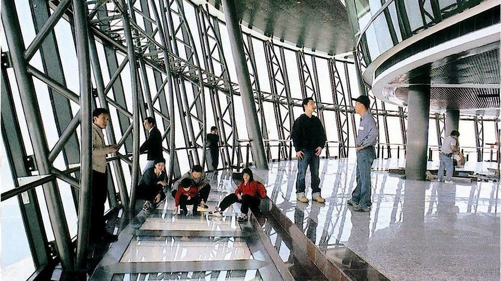 A group of people on the observation deck of the Macau tower