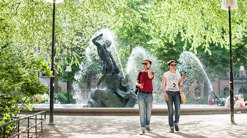 two women standing beside a fountain in stockholm