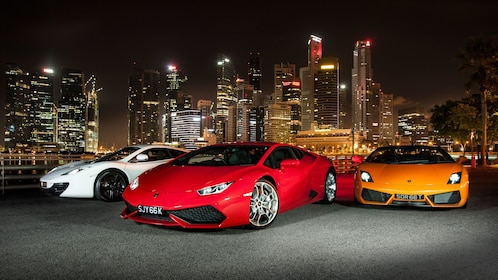 Three sports cars in front of Singapore skyline at night
