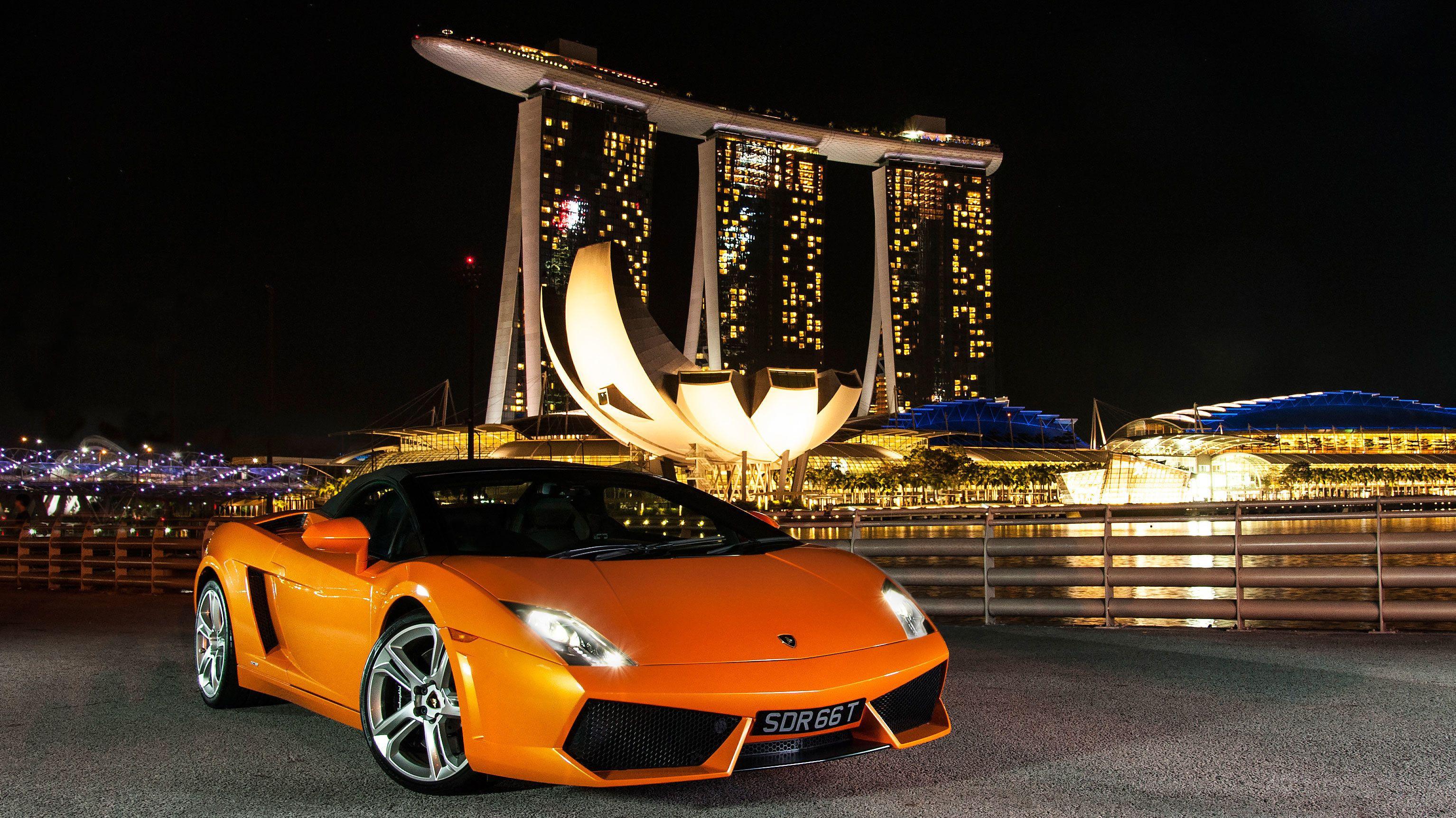 Orange sports car at night in Singapore