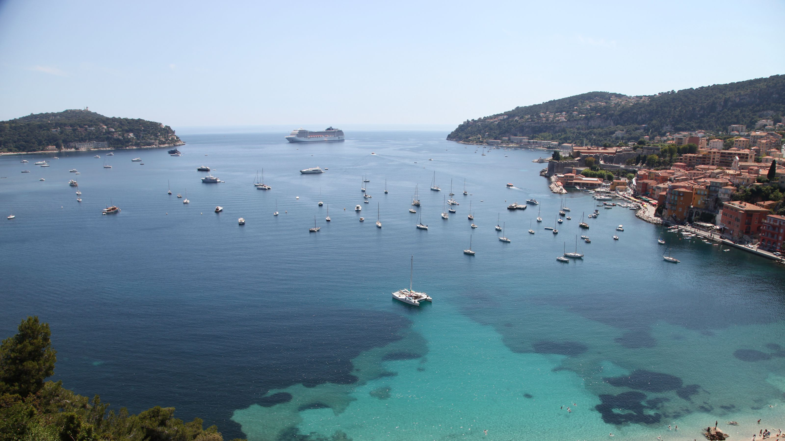 Scattered boats and cruise ship on the clear water in France