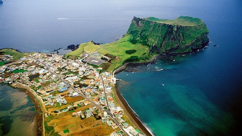 Aerial view of a city in Jeju and a vibrant green caldera