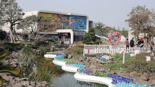 A modern building surrounded by glass sculptures in Jeju