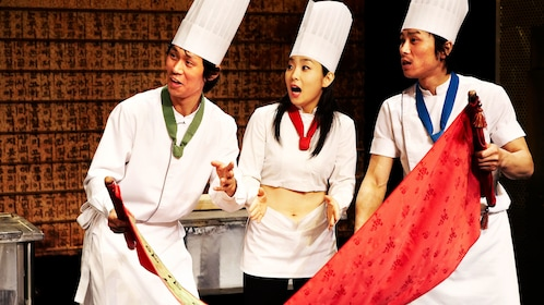 Three performers dressed as chefs looking at a scroll at Nanta Show