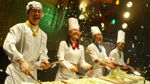Four performers dressed as chefs cutting vegetables at Nanta Show