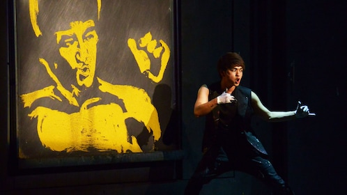 Performer posing infront of a painting of Bruce Lee on stage