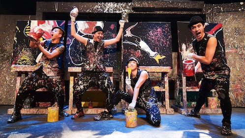 Four performers striking a pose infront of their paintings on stage