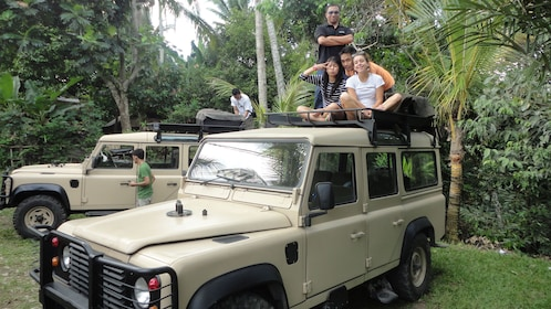 A few people sitting on top of a jeep in Bali
